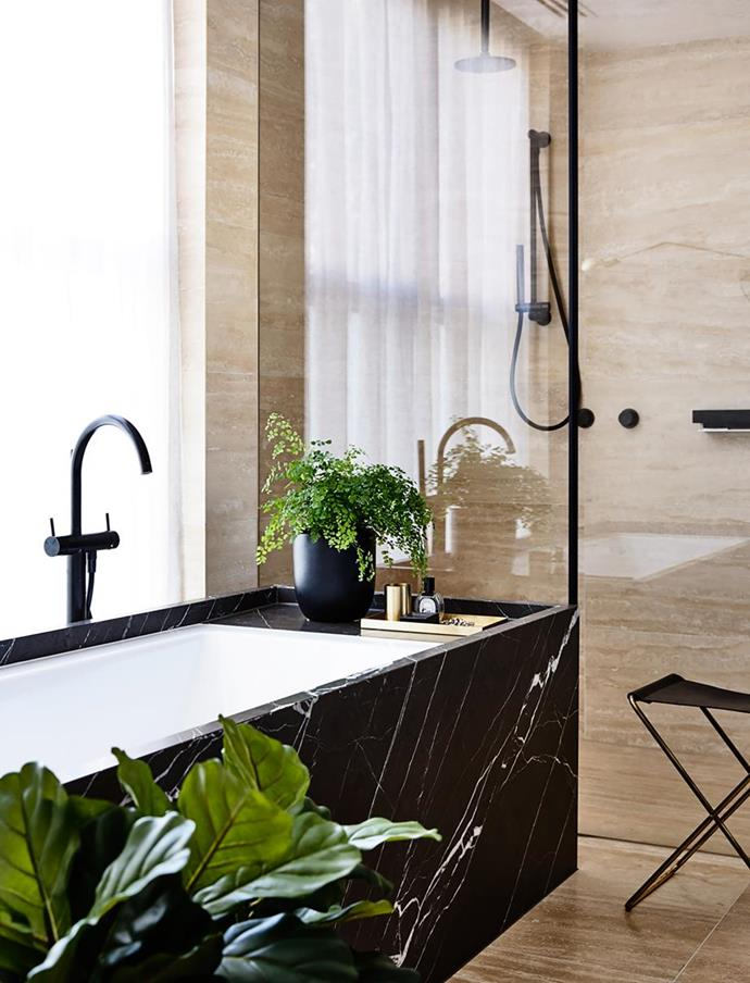 """Travertine tiles are a warm and soft background to the striking black Pietra Grigio marble bath in the bathroom of this [family home with a brutalist aesthetic](https://www.homestolove.com.au/functional-family-home-with-a-brutalist-aesthetic-20964