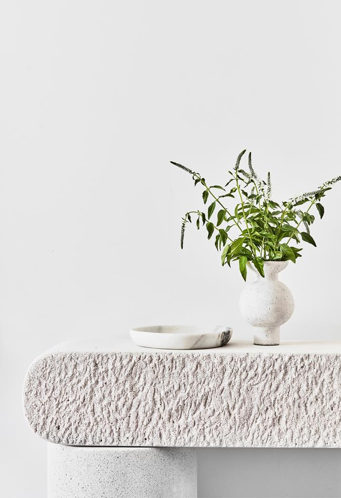A stone console table by Future Collective displays a Clae Studio vessel and Country Road marble tray.