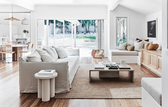 In stylist Kristin Rawson's home, a sofa and cabinetry from MCM House are teamed with a Trunk side table by Future Collective, stone coffee tables and a Bramble jute rug from Armadillo. The artwork is by Kate Bellm.