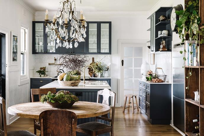 """Bec had her heart set on an ink-blue kitchen after her years living in London, where [colourful kitchens](https://www.homestolove.com.au/colourful-kitchens-6052 target=""""_blank"""") are popular. """"It's a very traditional country-style kitchen with lots of big cupboards,"""" says Bec. """"Angus and I are both tall, so we wanted to make sure the cabinets and benches were at a reasonable height."""" The dining table is from Storie in Melbourne, the chairs were an eBay buy and the chandelier is from Found in Daylesford."""
