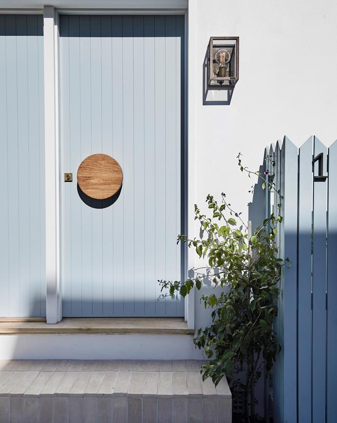 The side entrance is now the main entry. The tongue-and-groove front door was custom-made by Verdecon with a round Niki handle by Designer Doorware. Quadro wall light by Il Fanale from LightCo.