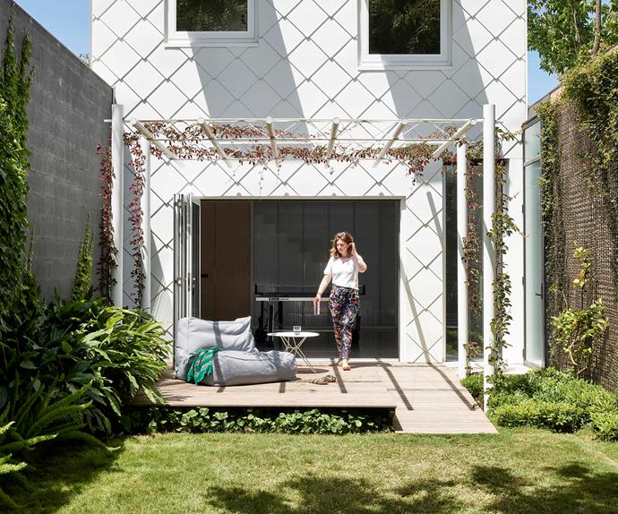 Woman on the back deck of a white pitched-roof home