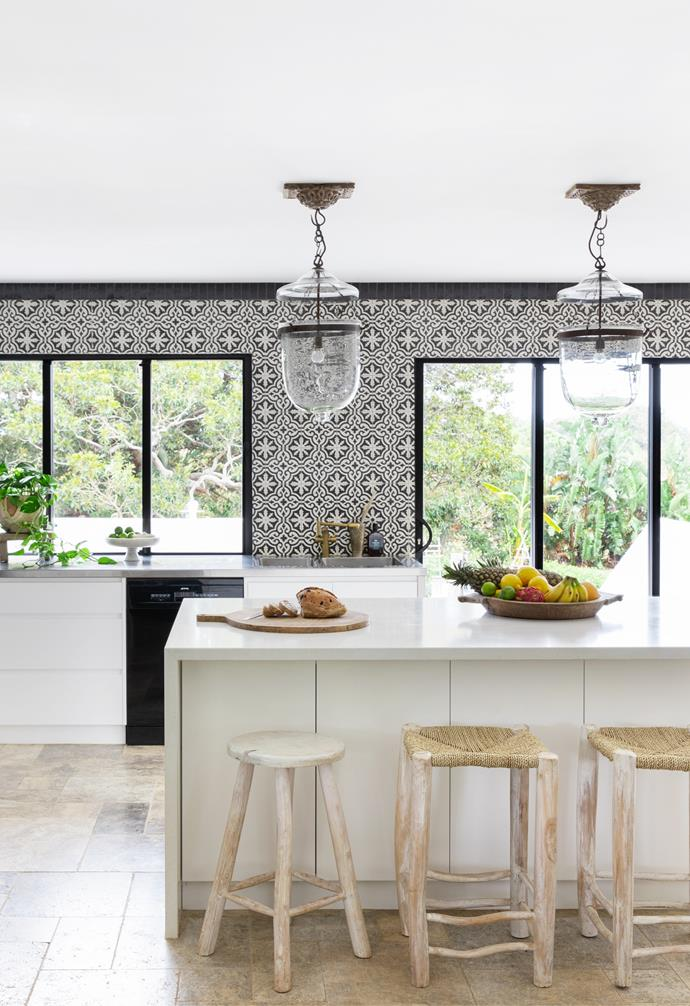 """Patterned Jatana tiles from benchtop to ceiling steal the show in the kitchen. """"I love to use a feature tile wherever possible and black and white is just classic,"""" says Amanda, who also chose black Smeg appliances and black-framed windows, with sliding doors that lead to the verdant backyard. """"It was really important to open the house up to the outdoors, which makes it seem so much larger,"""" she adds. An island bench topped in engineered stone, paired with rattan stools from Bisque Traders and a whitewashed timber stool, is a hub for informal family meals. A pair of Moroccan chandeliers from Ha'veli of Byron Bay completes the look."""