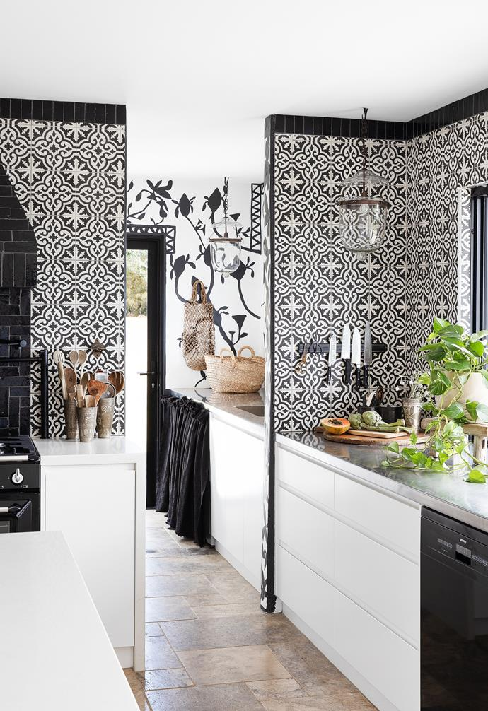 Beyond the kitchen, a hand-painted mural by Phoebe and Amanda upscales the laundry. Warm Ash Tumbled Travertine, laid in French Pattern, Beaumont Tiles.
