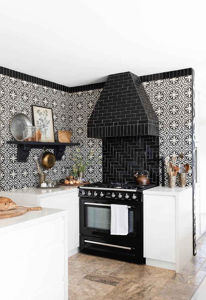 """I'm so inspired by the look and feel of Spanish villas,"""" says Amanda, who pored over pictures of European farmhouses while dreaming up the custom rangehood  tiled with Bijmat black handcut pavers from Surface Society. """"The cabinet maker and tiler were reluctant to do it because it was quite heavy, so it took a lot of time and convincing, but we achieved exactly what I was after."""" Offset with a Smeg freestanding cooker, the Bijmat tiles also run around the kitchen ceiling like a cornice, framing the zone and defining the stunning splashback wall."""