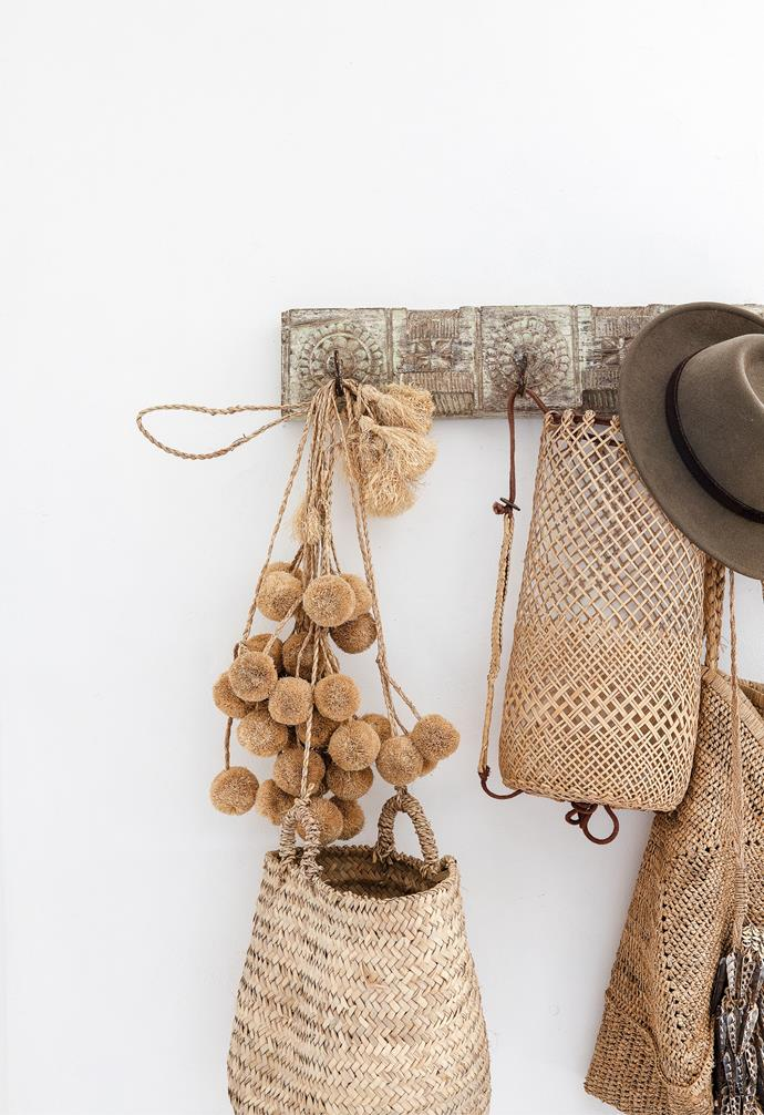 A Ha'veli wall hanger with pompoms from Casa Bohemia and assorted natural baskets.