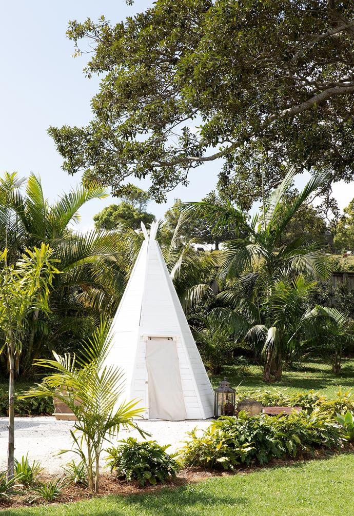 A Grand Wooden Teepee Hideaway from Plum sits in the garden. The pair enjoy roaming the outdoors, with its play areas, vegie garden and chicken coop.