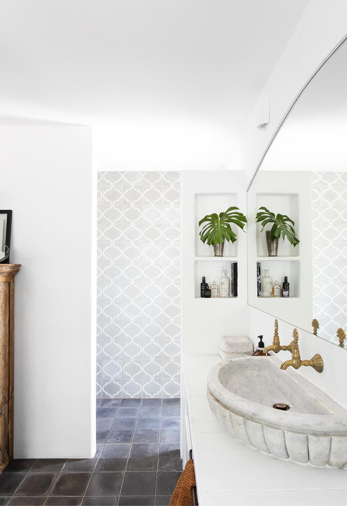 """In keeping with the rest of the renovation, the aim for the bathroom was to create a space that felt rustic and established rather than shiny and new. """"The design took shape around creating a bathroom without glass,"""" explains Amanda. Grey handmade floor tiles in a moody hue from Surface Society contrast beautifully with a rendered wall used to partition the wet area, defined with Grey Arabesque feature tiles from Jatana."""