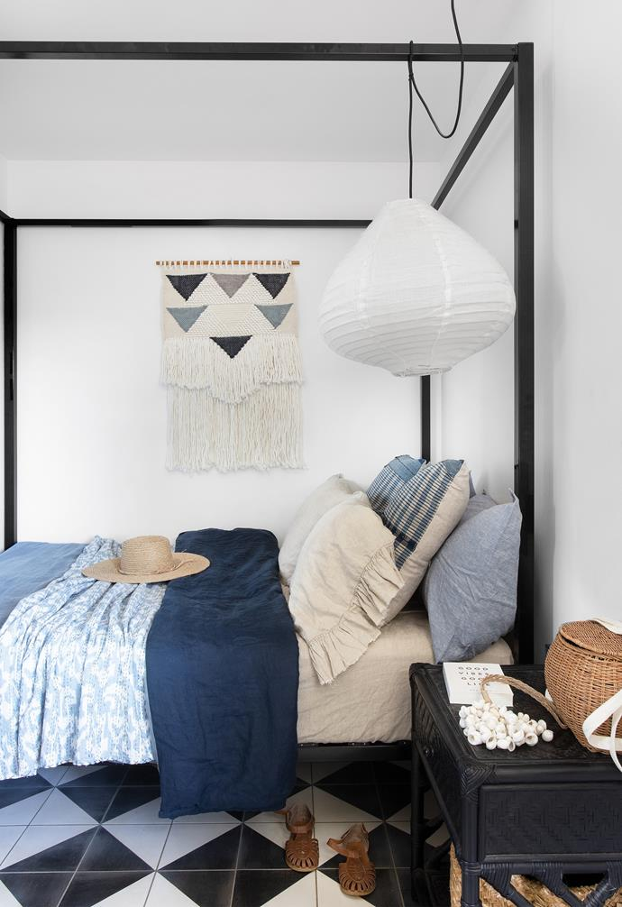 The children's modest-sized bedrooms are furnished simply, yet stylishly, as places to sleep. In Indiana's room, a steel-poster bed, sourced online, is layered in a mix of sumptuous textiles, including an I Love Linen quilt and pillowcases in Baby Blue Chambray, teamed with Ruffle bedding in Natural from Society Of Wanderers. The walls also showcase tactile materials, with the Network Rugs Scandi textured fringed wall hanging from Temple & Webster echoing the shapes on the tiled floor, while a cloth pendant from The Secret Room hangs above.