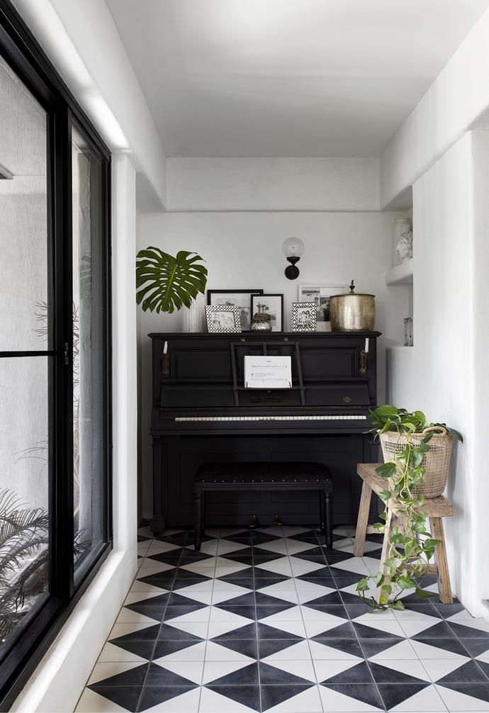 """Previously a veranda, this space was enclosed to create a hallway, where one end is the perfect width to accommodate a piano that has been in Brad's family for three generations and is often played by Summer. """"The piano's been every colour and we received it orange,"""" says Amanda, who quickly transformed the heirloom with a coat of Dulux Domino to complement the striking chequerboard tiles from Jatana on the floor. With an eye for detail, she ensured every element adds to the monochrome scheme, from the photo frames and concrete niches filled with white ceramics to the 'Glass Ball' gooseneck wall light sourced from Fat Shack Vintage. """"By sticking to a few key colours, there's a sense of calm and cohesiveness throughout the house,"""" she explains."""