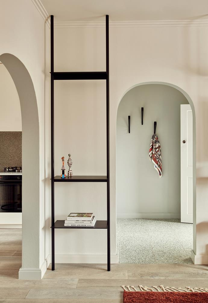 Even though the apartment is compact, the entrance makes a strong statement and is clearly demarcated with green terrazzo flooring from Signorino. The 3D die-cast zinc wall hooks add visual interest. A black steel shelving unit references the Art Deco balustrading on the building's external stairs.