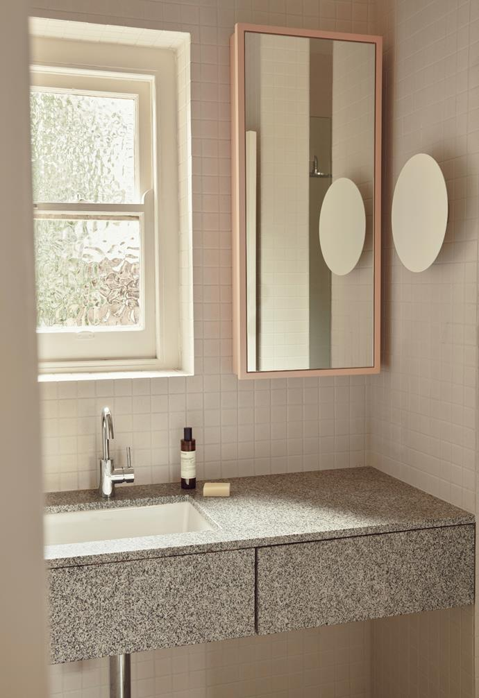The bathroom references the Art Deco period with atypical colours and materials, like pink on the cabinetry, small tiles and original mottled glass. An oversized wall hook and tapware from Astra Walker are contemporary elements and the Samkiel grey granite from Signorino is the same as used on the kitchen benchtop