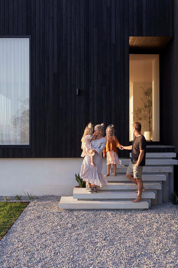 The Smith family hanging out on their beautiful concrete off-form steps, with the home's charred-timber cladding in sharp relief.