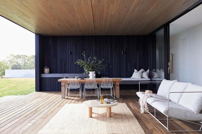 Relaxing is easy in this partially enclosed outdoor living zone overlooking the pool. The deck is rough-sawn spotted gum and the ceiling is blackbutt stained with white oil; the walls are clad with charred panels from Eco Timber. Bench seat in off-form concrete (black oxide) with cushions by The Dusty Road.