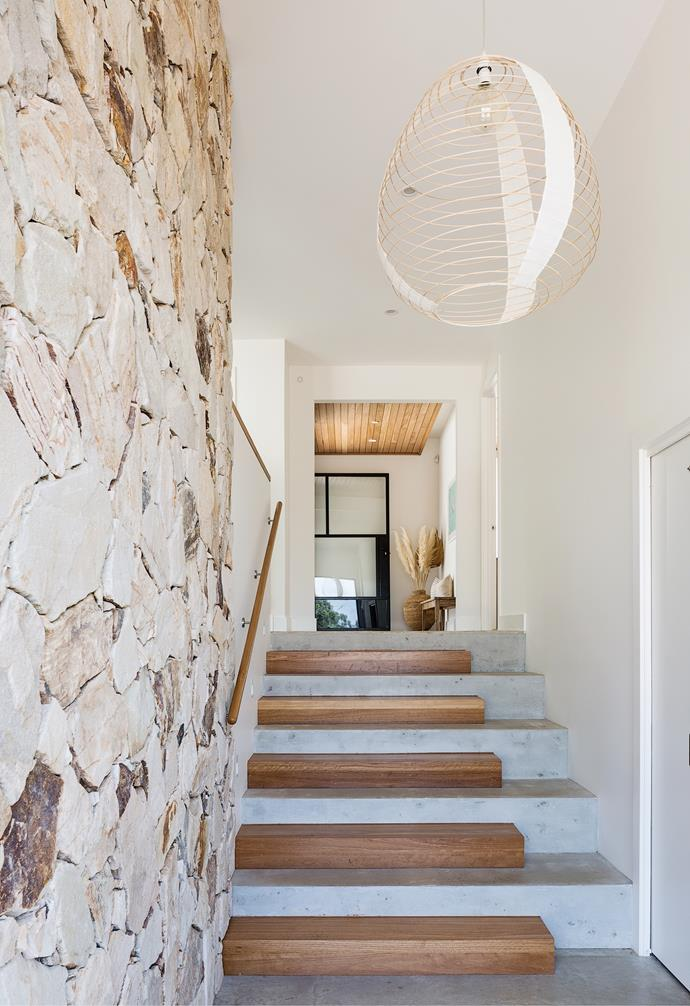 """With the staircase close to the front door, the homeowners were keen to do something different. """"Aaron had seen a full timber version of our stairs and thought a half-concrete, half-timber design would look great,"""" says Heather. The warm tones of the blackbutt [timber floorboards](https://www.homestolove.com.au/types-of-timber-flooring-1809