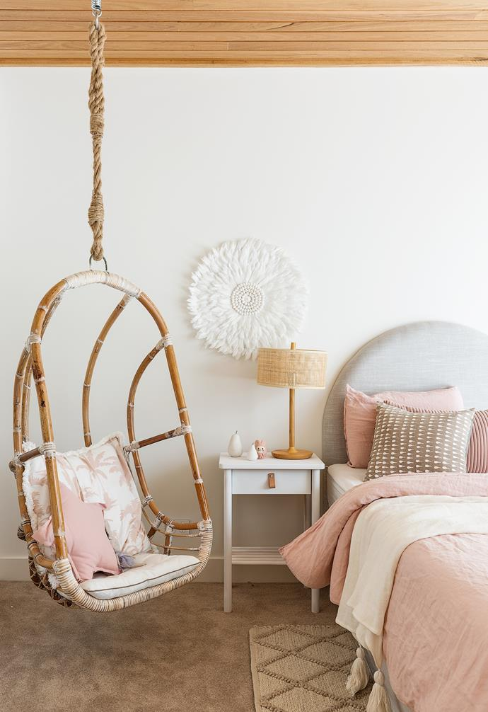 """Heather wanted to create a cute and feminine room for Stella before she gets older. """"I chose a more muted palette but used pink as she is my only girl and probably won't like pink forever,"""" she says. A hanging chair from Barbara's Storehouse, adorned with a 'Luana' European pillowcase from Linen House and 'Stella' star cushion from Freedom, makes a beautiful focal point. The pink tones continue in a 'Vintage' washed linen quilt cover in Nude Pink by Home Republic from Adairs. An arched Demi bedhead in Trinity Silver from Beds Ahead and a white Juju Hat from Rose Avenue add a touch of whimsy, while the 'Mitre' floor rug in Ghost from Weave and 'Shore 1' lamp from Beacon Lighting deliver earthy goodness."""