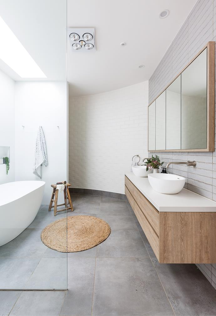 """A curved brick wall at the front of the home (designed to hide the front door from the street) makes a shapely statement in the family bathroom. """"The bathroom sits here as it didn't require a window,"""" says Heather. Instead, a large skylight invites natural light in, while an extra section of wall hides the toilet – a practical feature in a large, open wash zone."""