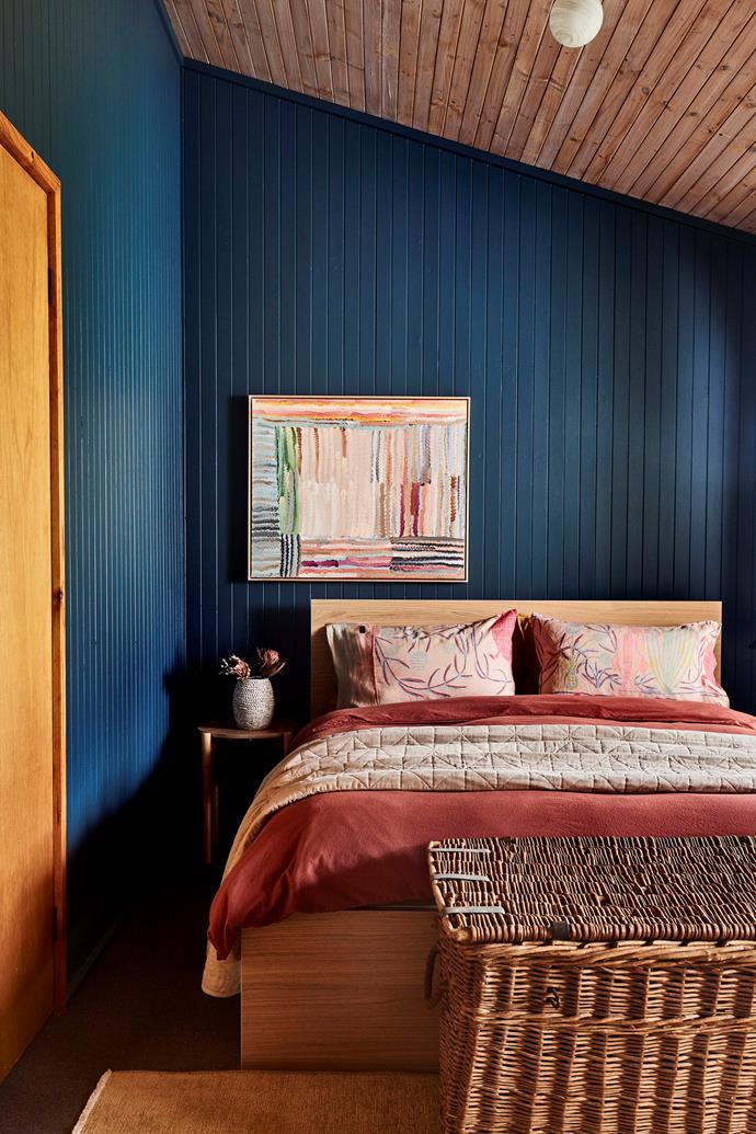 Known as The Blue Room, this space feels removed from the rest of the cabin. The artwork by Emma Cleine introduces shades of red and pink that recur on the bed linen.