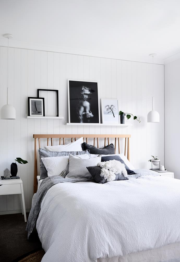 """""""Because it's our personal space, we deliberately designed the master bedroom  to be more masculine, with darker accent colours,"""" says Az, referencing the tan leather Nathan + Jac cushion, Maker And Hound bedside cabinet and Ikea black floor lamp. Evocative artworks above the bed are all characteristics of Scandi interiors and mostly connected to nature. """"The broom is a photo of mine, Az drew the face and others are of Scandinavia,"""" says Jamie. """"We like to tell a story with our galleries – this one has personal references and pictures that resonate with the tree, a longifolius ficus, next to our bed."""""""