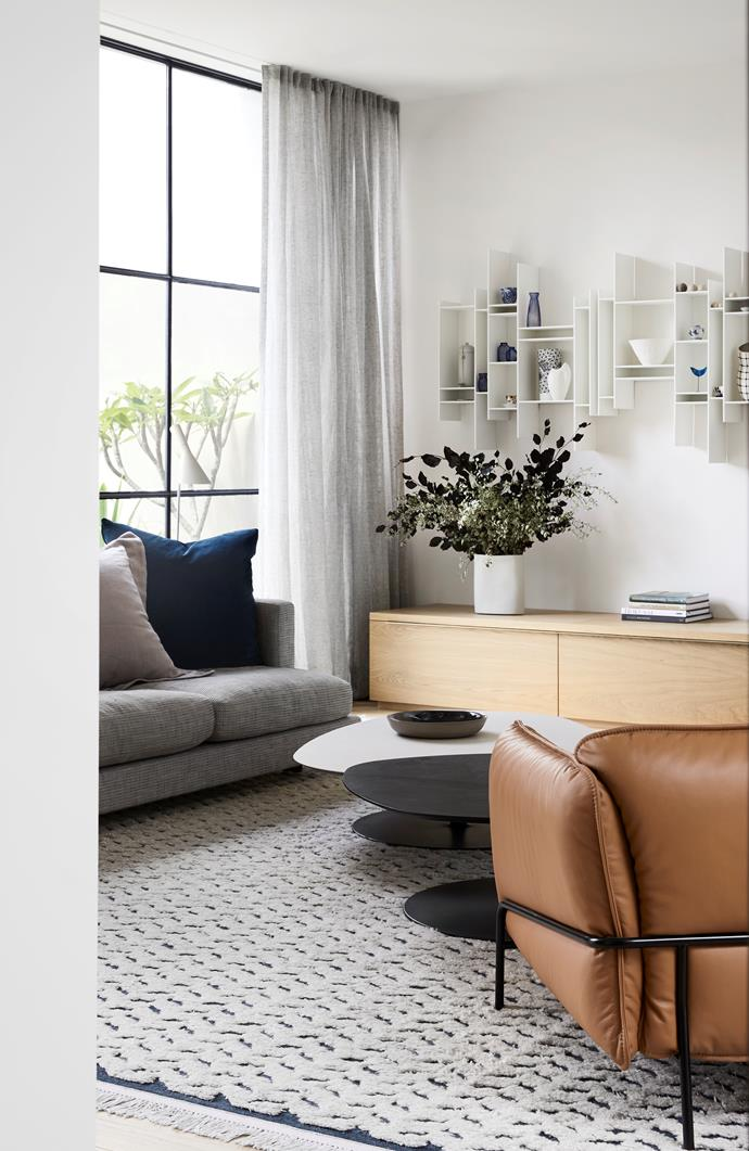 The informal living area connects to the dining room, and both benefit from a northern aspect with floor-to-ceiling glazing. Moroso 'Phoenix' coffee tables by Patricia Urquiola from Hub. Swedese 'Continental' easy chair from Fred International. Vase and bowl from Mud Australia