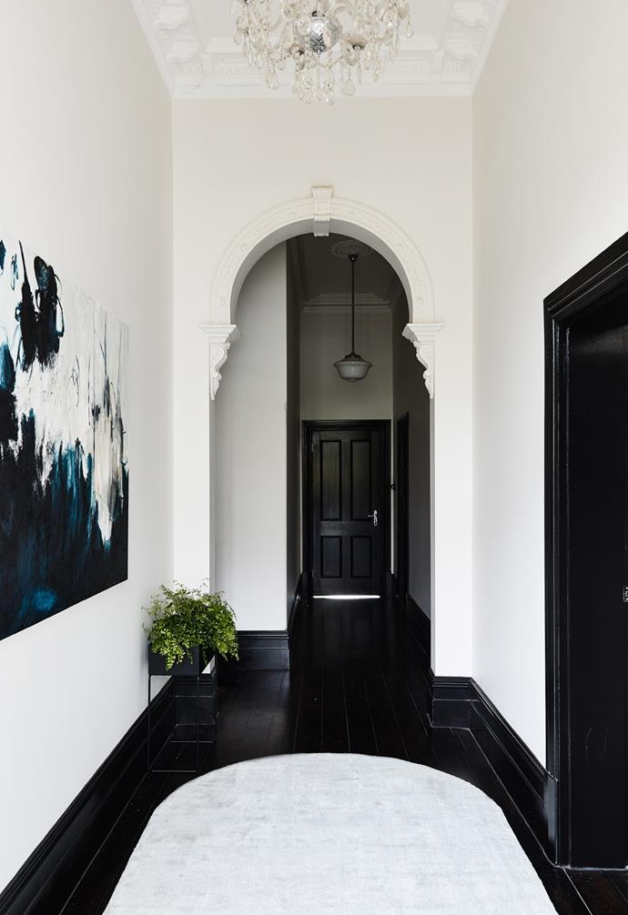 """Worlds collide in the entryway. Marked by dramatic [dark timber flooring](https://www.homestolove.com.au/what-is-black-japan-flooring-14511 target=""""_blank""""), high ceilings and delicate arches, the meeting point showcases a romantic yet contemporary ode to a bygone era. The artwork is by Kate Debbo, the lighting is from Schots and the plant box is by Ferm Living."""