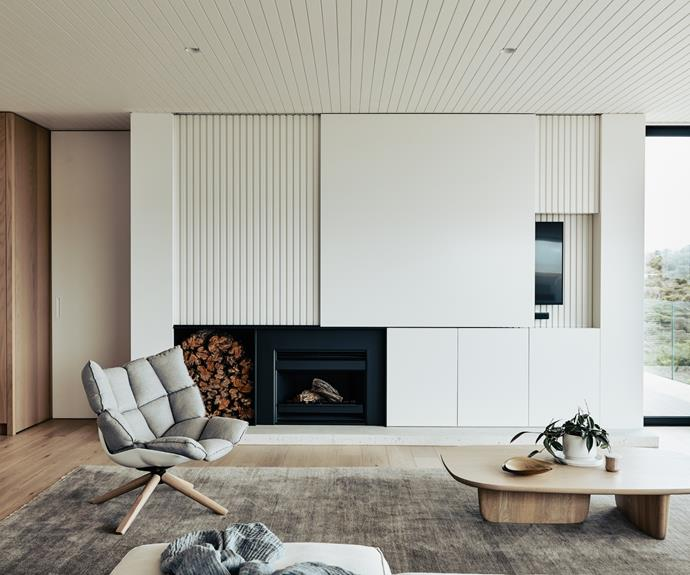 In the living room, a well-appointed B&B Italia 'Husk' swivel armchair is the best seat in the house with the fireplace, television and ocean within immediate sight while Armadillo rugs soften the mostly wood palette.