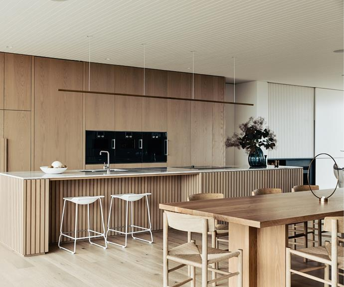 Adjacent to the first floor kitchen is a concealed hub and drop zone that conceals daily mess and kitchen paraphernalia. Tucked away to the left of the oven and fridge behind an unassuming, seamless door is a walk-in pantry with smaller appliances. To the right of the Gaggenau oven is a home bar secreted behind sliding doors, easily accessed when guests come by but camouflaged when not in use.