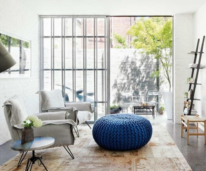 Industrial style living room with blue ottoman