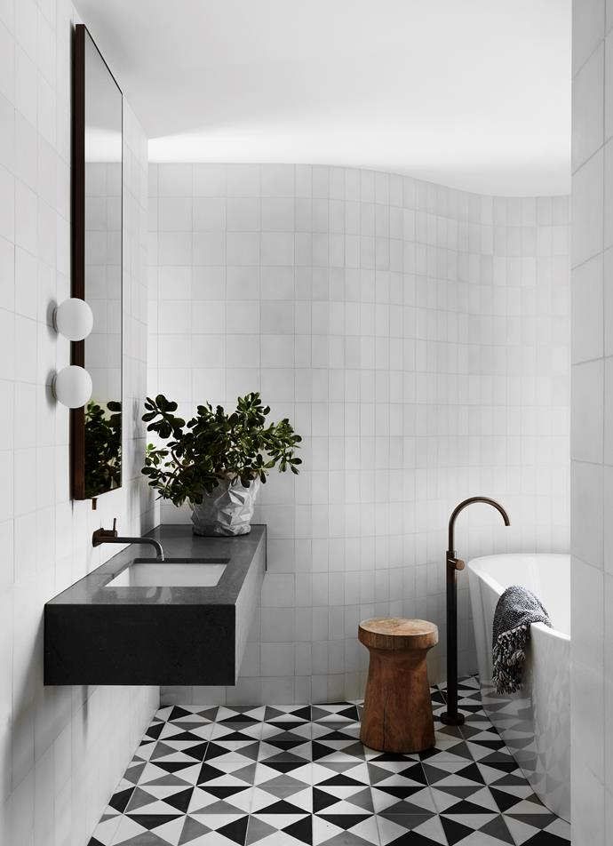 The children's bathroom has custom floor tiles from Popham Design and a Basaltina vanity. Brodware tapware, bath and basin from Candana. Flos 'Glo-Ball' wall lights from Euroluce. Timber stool from Orient House. Loom towels.