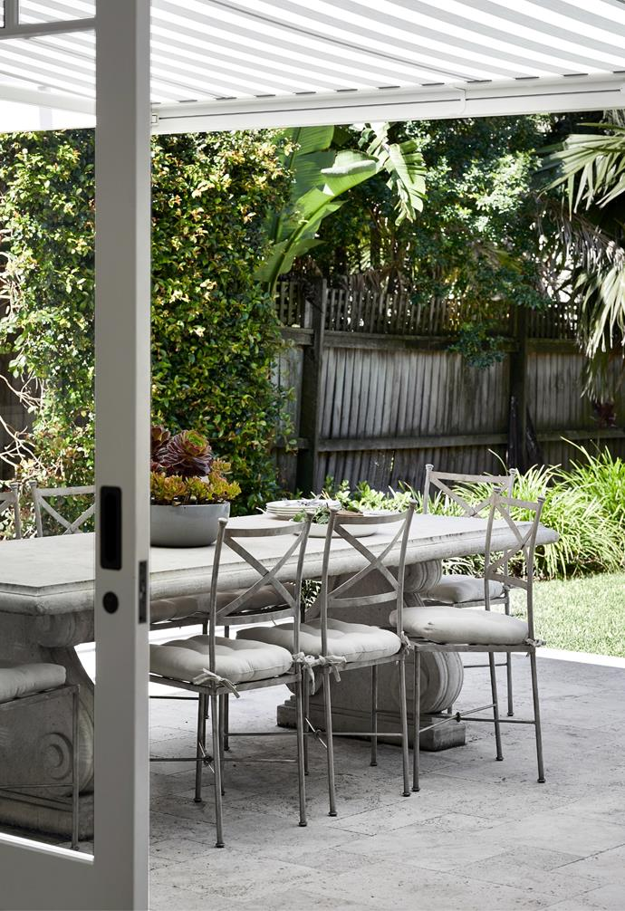 """The rear extension of this Federation-era abode is a timeless take on open-plan living. """"I wanted the house to flow nicely, without stepping from one century to the next,"""" says Rachel, a part-time decorator. While the colonial-style windows supplied by Cadence & Co make her feel closer to her roots, the alfresco dining area reminds her of holidays in Tuscany. Travertine paving from Amber offers a chic base while the table from Early Settler and Yardware chairs create an opportunity for year-round dining."""
