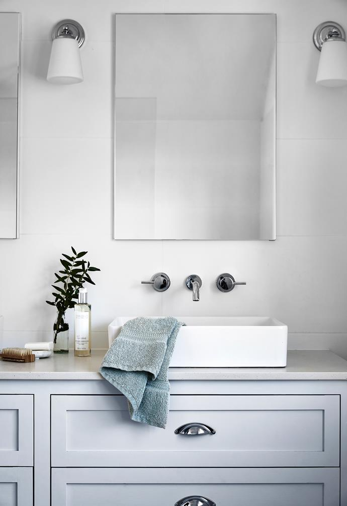 The ensuite vanity has two 'Cielo' basins from Highgrove Bathrooms and Phoenix tapware from Reece. The vanity is painted in Porter's Paints Mist and has Caesarstone 'Fresh Concrete' benchtops, while the wall sconce from Emac & Lawton mirrors the classic look.