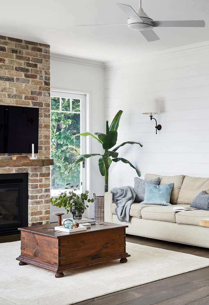 """A soft colour palette of whites, greys and dark timbers culminates in the open-plan living and entertainment areas. VJ panelling from InTrim on the walls pays homage to Rachel's style muses: colonial-style queen India Hicks and UK brand, The White Company. """"It was a large expanse of wall so I wanted a subtle feature,"""" says Rachel. The 'Soho' wall sconce from Emac & Lawton continues the timeless look as does the Oz Design sofa that was bought before renovating."""