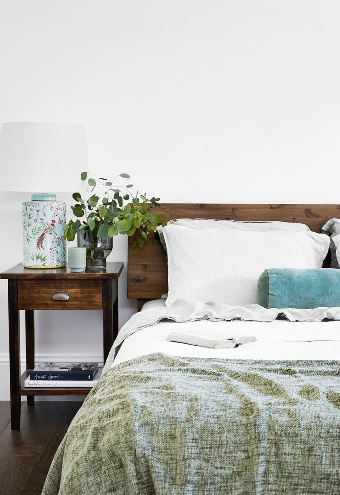 """Peacefulness was the watchword for Rachel and Rolf's bedroom. Rachel called on the garden outlook using dark timber for the bed and bedside tables with green touches, including the 'Claydon' lamp from Not Brand and quilt from Debenhams. """"I love a natural palette and nothing fussy,"""" says Rachel, who chose linen sheets and a duvet from Sheridan."""