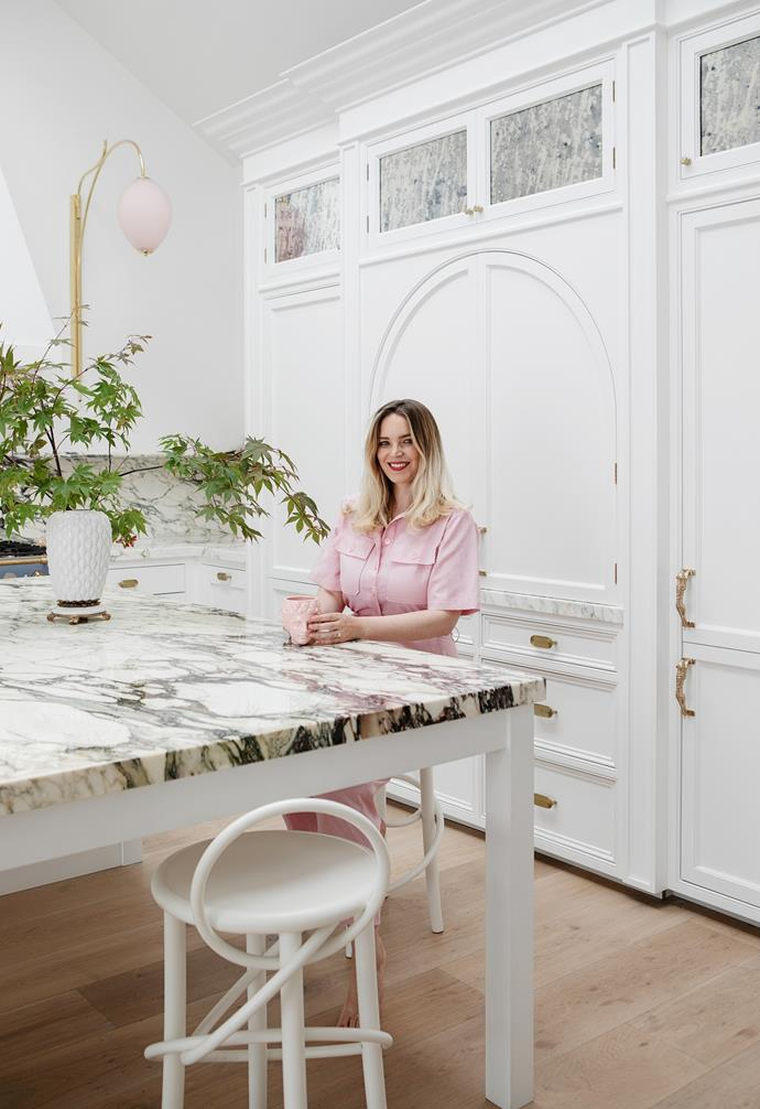 Suzie sits in front of the kitchen's custom joinery by Newcastle Design. This practical storage was inspired by the Victorian-era front door.