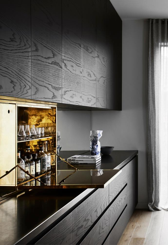 """Japan-stained timber joinery in the dining area is punctuated by a custom brass cocktail cabinet in this moody space conceived by [Powell & Glenn architects](https://www.homestolove.com.au/modern-concrete-home-22848/ target=""""_blank"""")."""