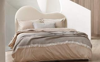 Neutral bed with a curved boucle bedhead