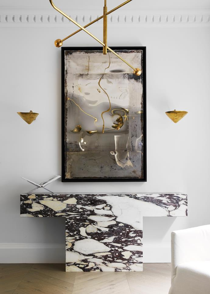 Perspex book holder from Taschen. The Wonderland wall sculpture by Dylan Farrell. Console in Viola marble designed by Phoebe Nicol.