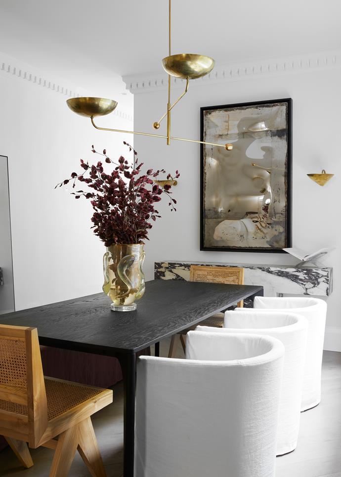 The 'Huxley Curve' dining table from GlobeWest is attended by custom slipcovered armchairs by Phoebe Nicol and Pierre Jeanneret chairs. Murano vase from The Vault Sydney. Light fitting designed by Phoebe Nicol.