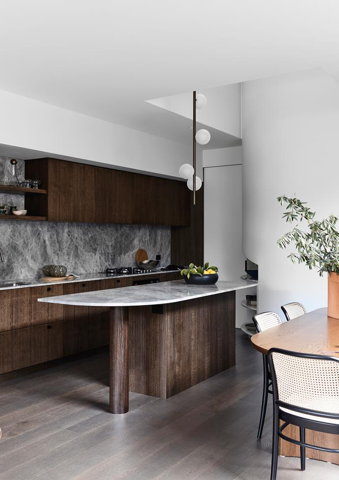 Kitchen joinery in stained solid Tasmanian oak and quarter-cut veneer and honed dolomite in Silver Ash on benchtops and curved shelves. Fisher & Paykel oven and cooktop from E&S.