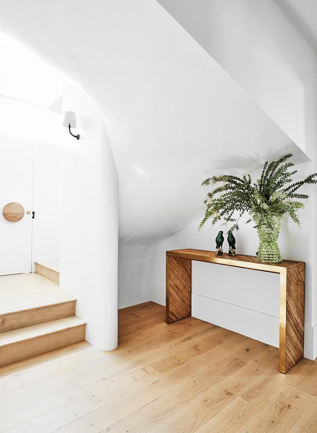 """interior designer Tania Handelsmann of Handelsmann+Khaw kept the decorating to a minimum in the airy entryway of this [coastal abode](https://www.homestolove.com.au/beach-bungalow-contemporary-renovation-22831/ target=""""_blank""""). The scultpural staircase has been finished in otsumigaki polished plaster."""