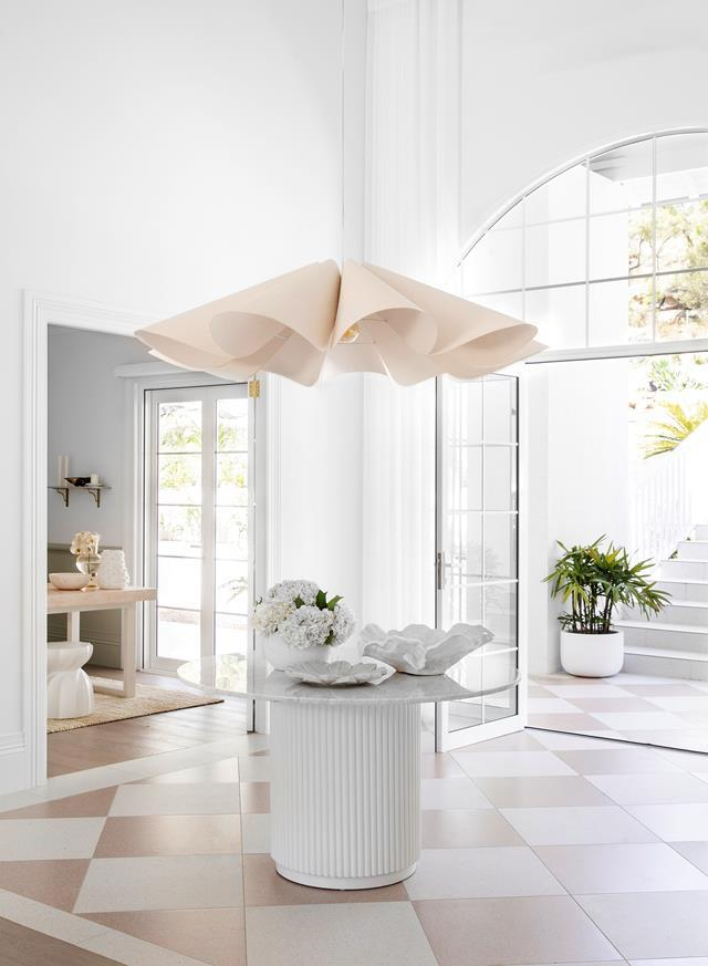 """A large glass arched window and glass front doors allow light to flood this [resort-style home](https://www.homestolove.com.au/resort-style-home-three-birds-renovations-22500/ target=""""_blank"""") by Three Birds Renovations' spacious entryway."""