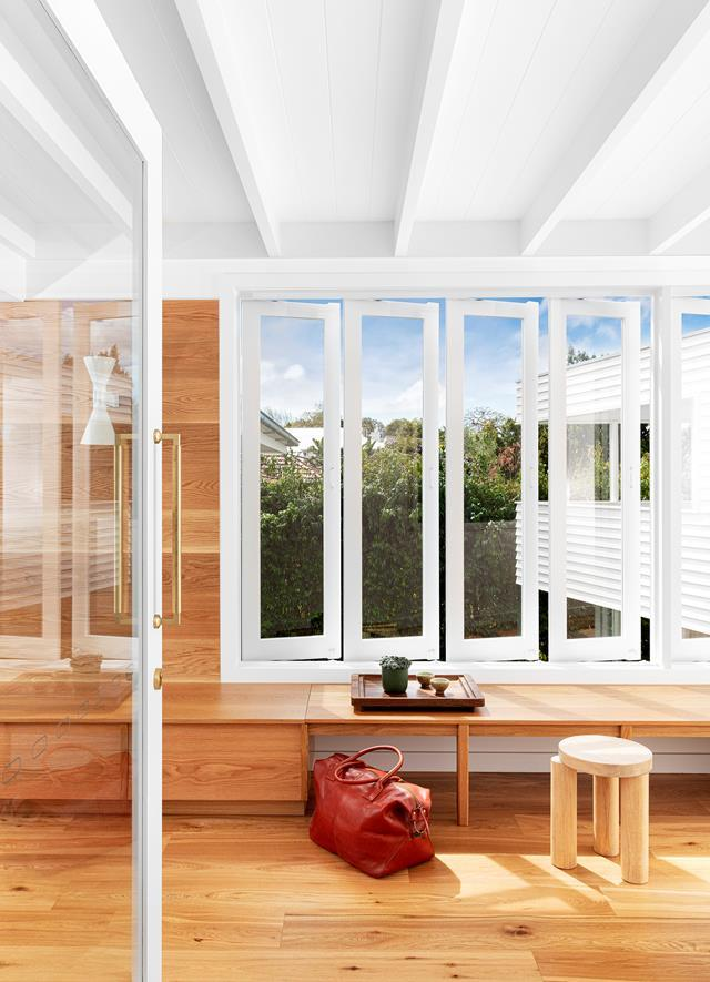 """Clad in white-painted battens, the entrance and walkway of this [renovated Queenslander](https://www.homestolove.com.au/renovated-1950s-queenslander-extension-22262/ target=""""_blank"""")  functions as a light well and breakout space, and eases the transition between old and new."""