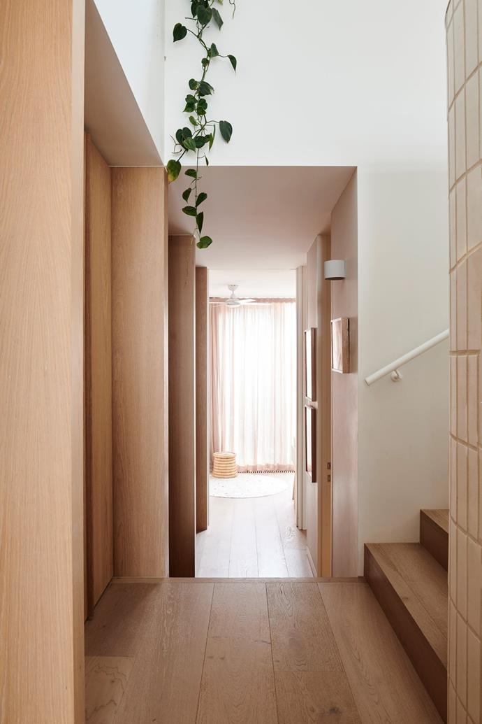 A curved hallway provides a transition to the home's three bedrooms.