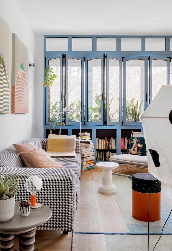 A sequence of windows open the living space up to the plant-filled terrace, while shelves underneath demonstrate the family's love of reading. In front, an Ikea 'Havsten' armchair is topped with a cushion by Lindell & Co. A round coffee table from the Elefanti series by AMArchitectrue holds a Flos 'Lampadina' lamp by Achille Castiglioni.