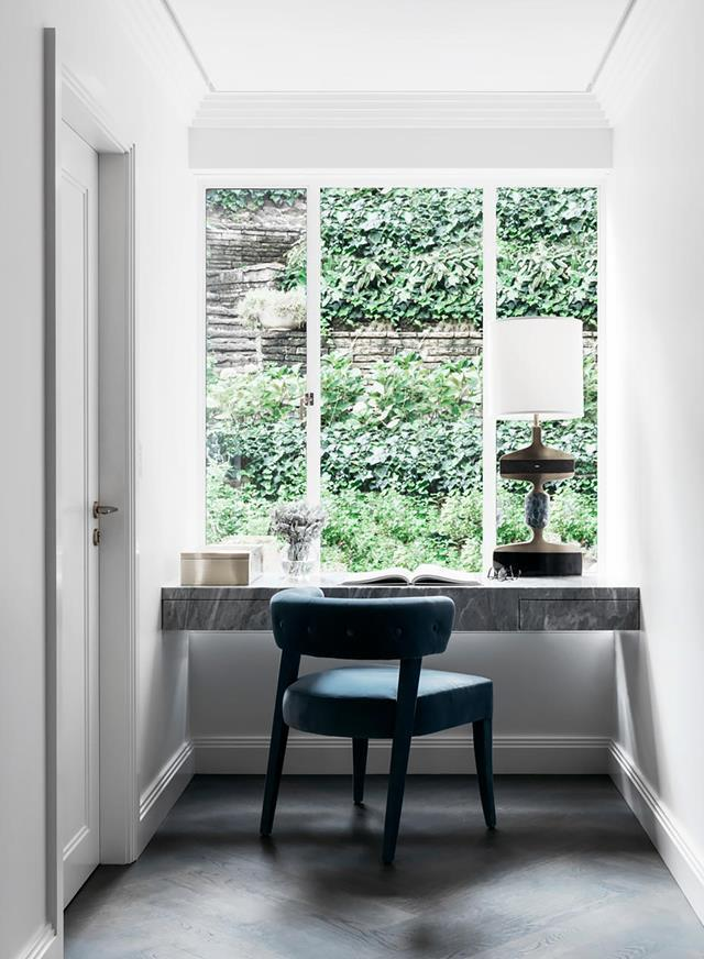 """A teal velvet buttoned chair and agate-encrusted brass lamp make the hall desk within this [restored 1930s apartment](https://www.homestolove.com.au/restored-1930s-apartment-21800/