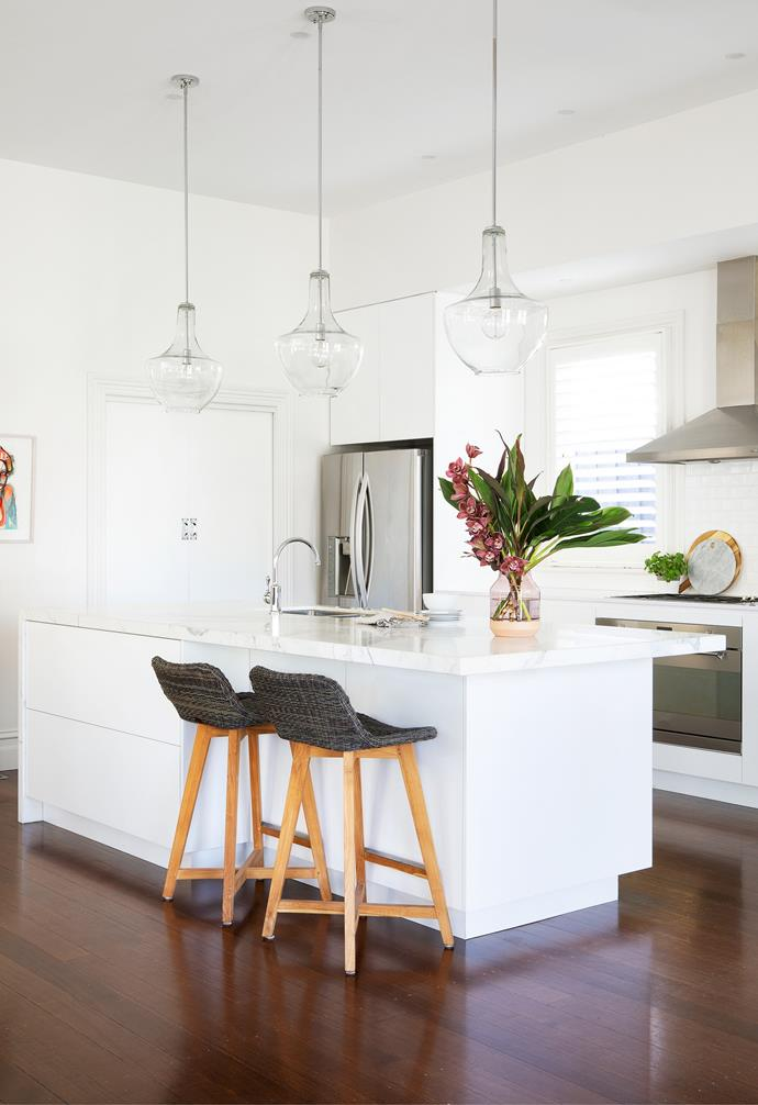 """Tucked away in the corner of the open-plan living area, the kitchen was previously defined by square terracotta tiles. """"As soon as we ripped those tiles out and polished the floorboards underneath, the whole space just opened up,"""" explains Jenefer. Next, they removed the existing L-shaped benchtop and island bench. """"Vicki fell in love with a huge slab of Calacatta marble with the most beautiful vein running through it, so we covered the island in that and used engineered stone from Silestone for the other benchtop,"""" says the designer. One of Vicki's must-haves was an island that could double as her work space, so Jenefer added two drawers to hold stationery and files, and carefully hid powerpoints near the seating area, which features Skal kitchen stools from Satara. Three glass pendant lights from Custom Lighting complete the statement look."""