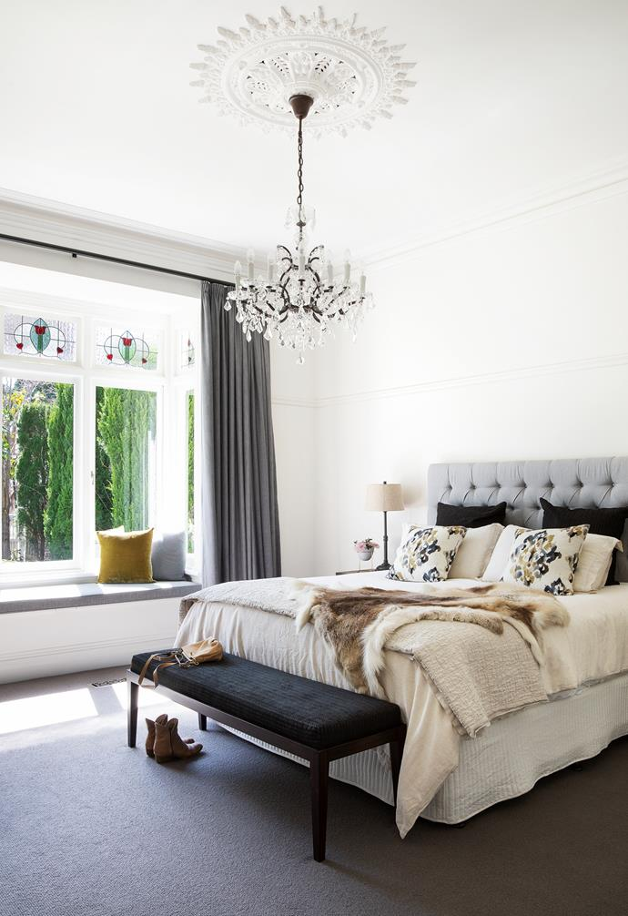 """The must-have in the bedroom was a chandelier and, after searching high and low, they eventually had the larger Rococo iron and clear crystal round chandelier shipped in from Restoration Hardware in the US. """"It really brings period features in the space to life, especially the ceiling rose,"""" says Jenefer. The My Side 'Series 6' mattress and base from Forty Winks, along with the ottoman bench from Boyd Blue upholstered by Geissel Reed in Seneca 'Quin Onyx' fabric and custom- made curtains, create a hotel-luxe vibe"""
