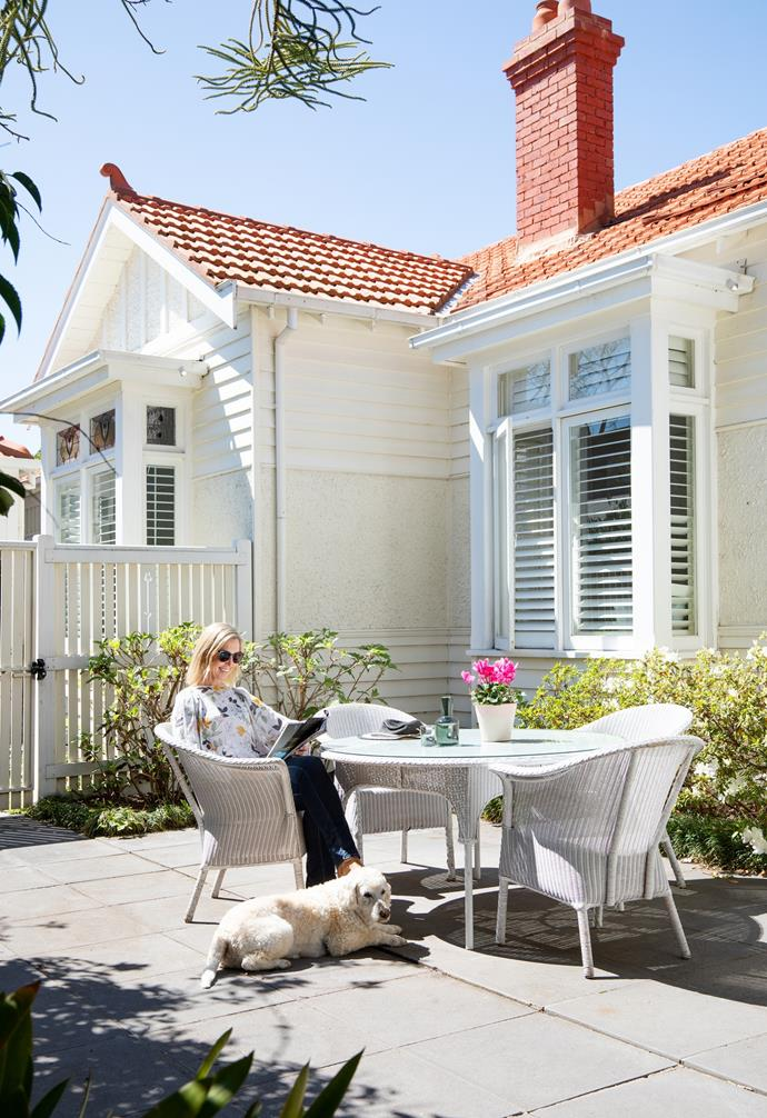 """The existing garden reflects the cottage style of the home, with lush plantings of pansies, alyssum and meticulously tended hedges. """"Now that the interior is done, we're about to embark on the exterior,"""" explains Vicki, pictured, relaxing with Jasper in the quaint space off the dining and living areas."""