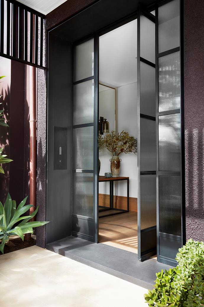 The front entrance has steel and glass doors from Steel Windows Australia. On entry console, ceramic vessel by Jann Kesby from Bess. Sydney Sandstone paving from Gosford Quarries.