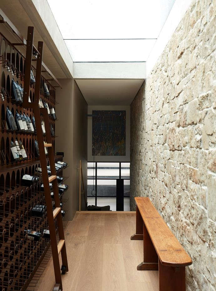 The wine cellar links the garage and rumpus room with the rest of the house. Libreria del Vino wine wall system from Living Edge with 'Clancy' sandstone rubble wall opposite from Eco Outdoor.